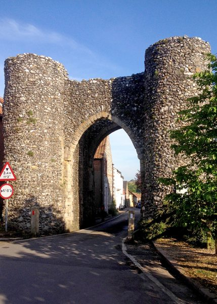 Stone and flint bailey gate with towers and an arched entrance, Castle Acre, England, UK